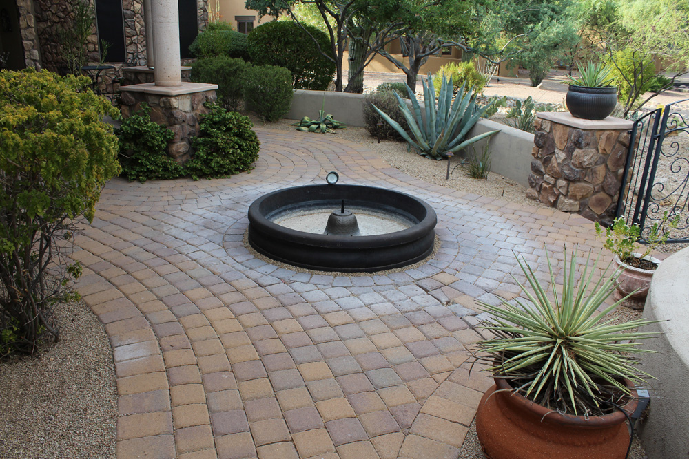 Concrete pavers before with mineral ring on pavers around fountain